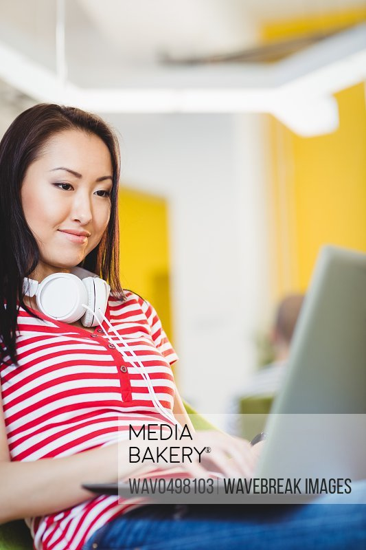 Happy beautiful young female executive using laptop at creative office