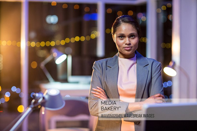 Beautiful businesswoman standing with arms crossed in office at night