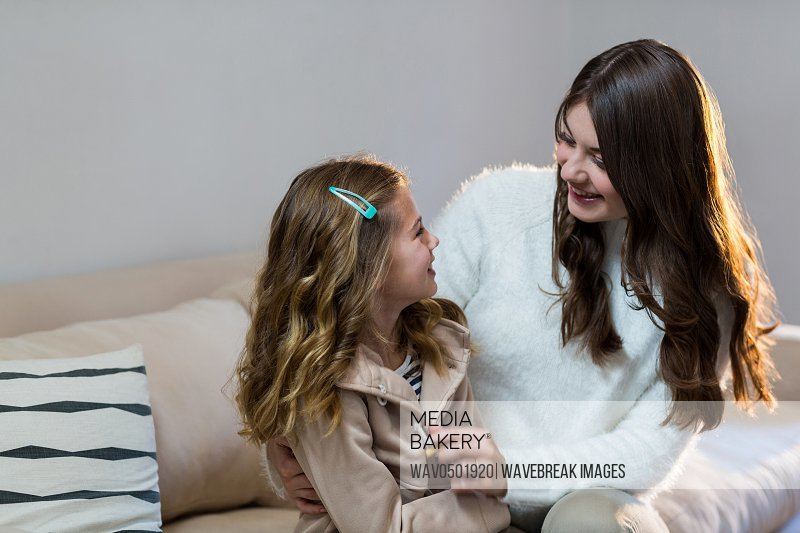 Mother and daughter looking at each other at home