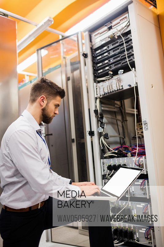 Technician using laptop while analyzing server in server room