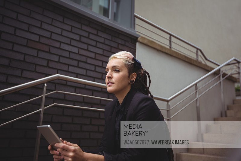 Businesswoman holding digital tablet in office campus