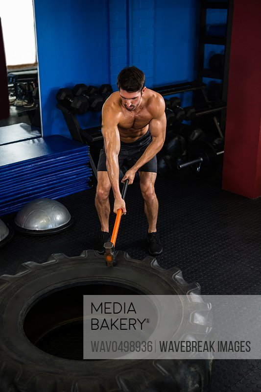 Full length of young man exercising with sledgehammer in gym