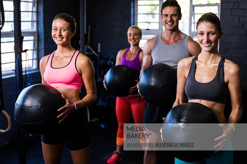 Portrait of happy athletes exercising with fitness ball in gym