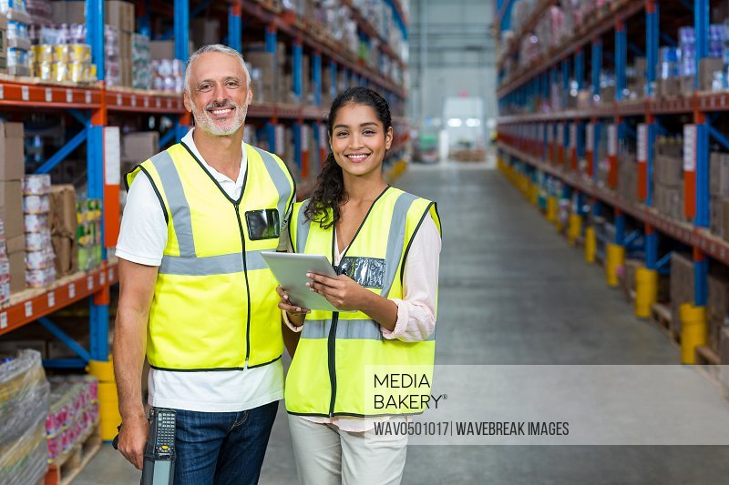Portrait of warehouse workers standing with digital tablet in warehouse