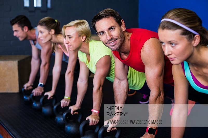Portrait of smiling man exercising with athletes in gym