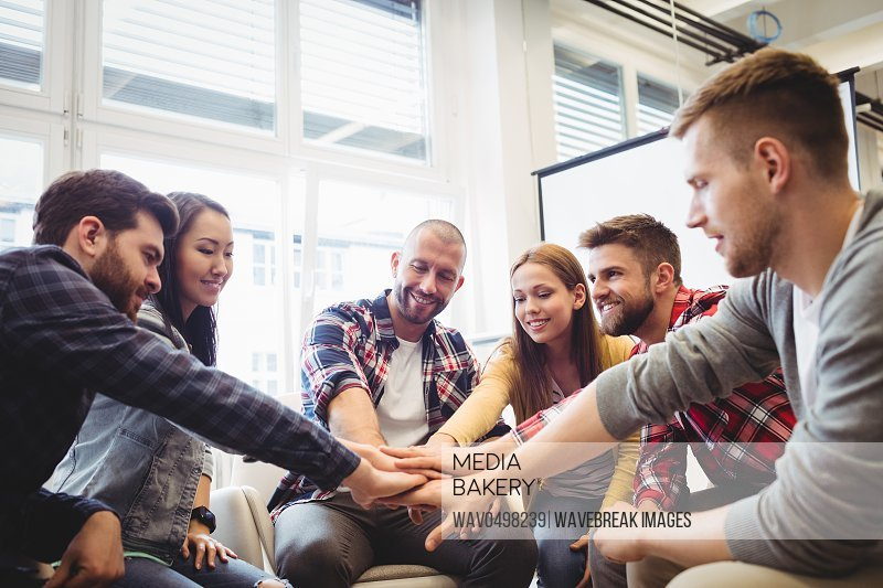 Smiling creative business people stacking hands in meeting room at office