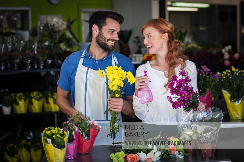 Couple holding bunch of flowers and spray bottle in the flower shop