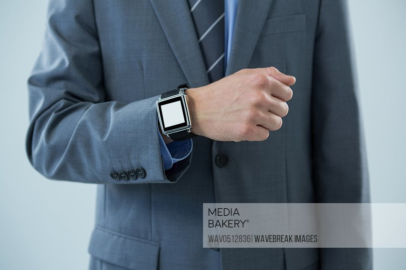 Mid section of businessman showing his smartwatch