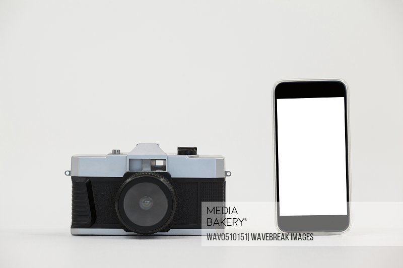 Close-up of camera and smartphone against grey background