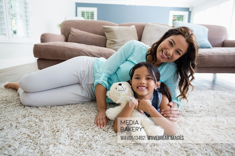 Portrait of happy mother and daughter lying on rug
