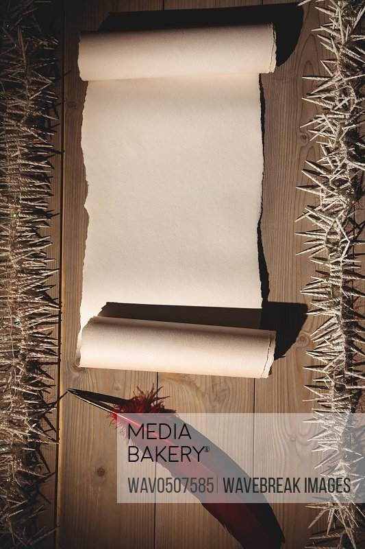 Old blank scroll paper and quill on wooden table
