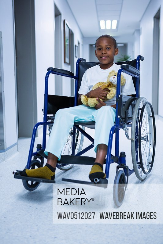 Portrait of boy sitting on wheelchair and holding teddy bear in corridor at hospital