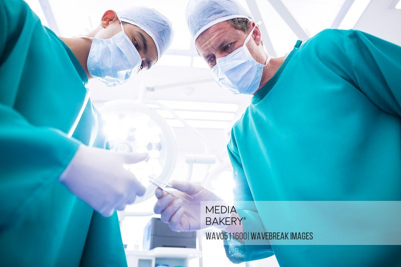 Surgeons performing operation in operation room at hospital