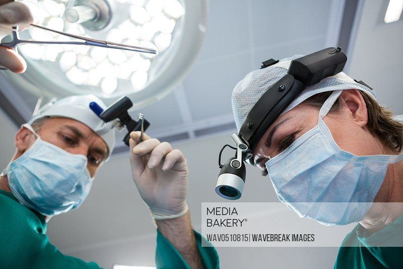 Surgeons holding surgical tool while operating in operation theater