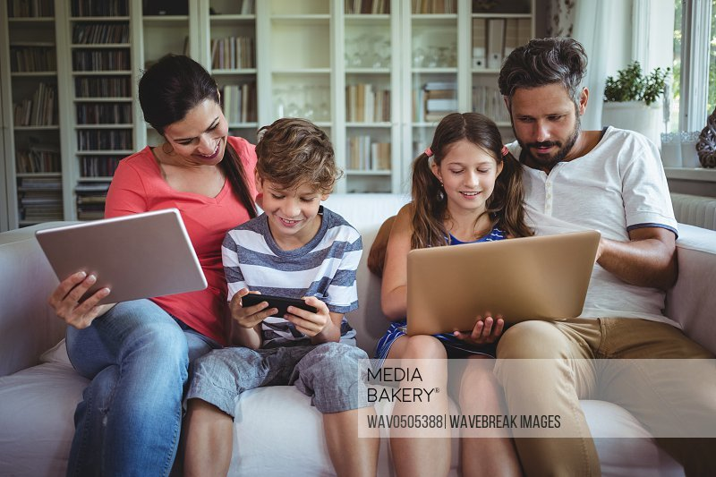 Happy family sitting on sofa and using laptop mobile phone and digital tablet at home