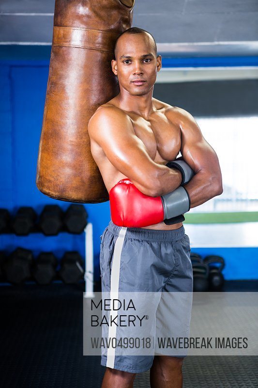 Portrait of confident male boxer standing by punching bag in gym