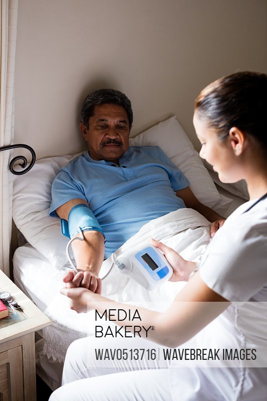 Doctor checking blood pressure of senior woman