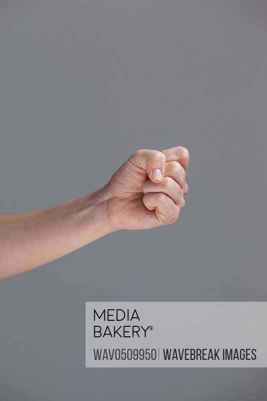 Close-up of clenched fist of a woman against grey background
