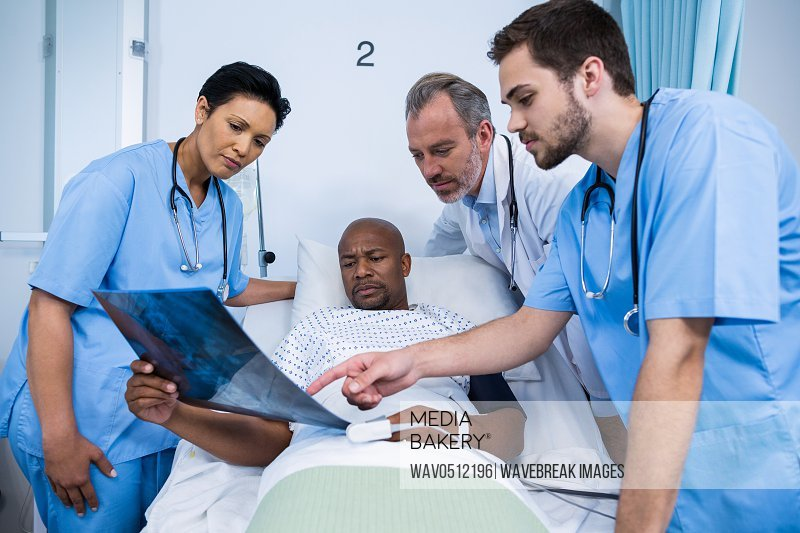 Doctor and nurse discussing x-ray with patient during visit in ward