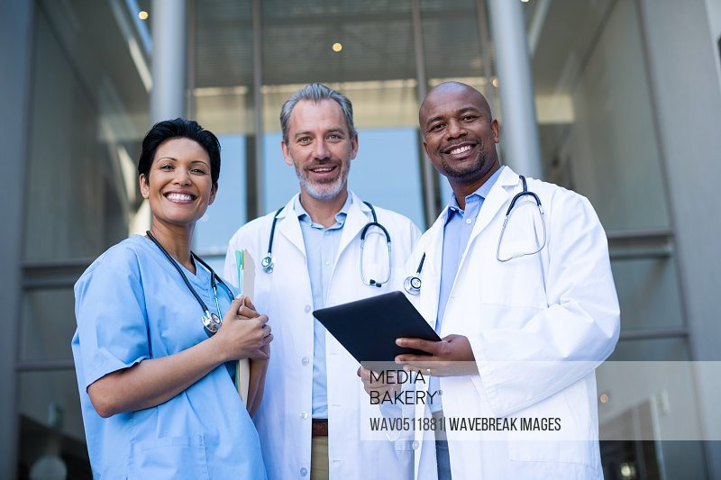 Portrait of surgeons and nurse standing of hospital