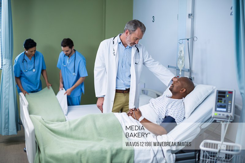 Doctor interacting with patient during visit in ward