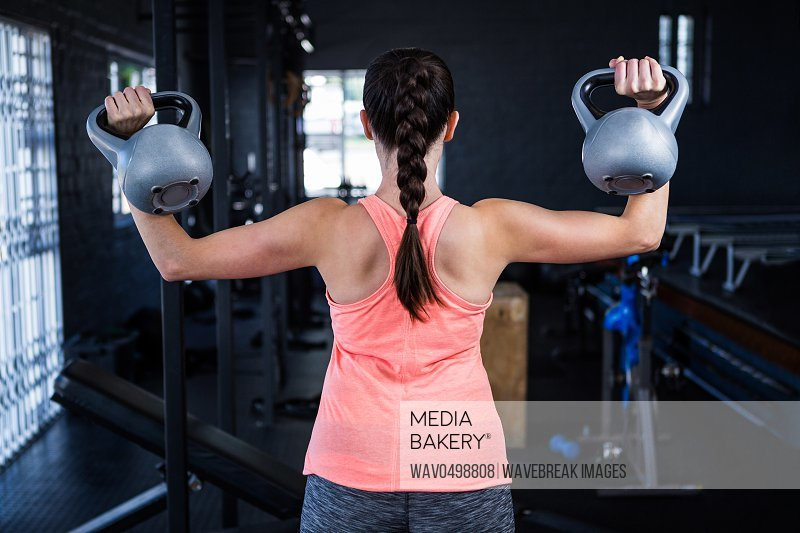 Rear view of athlete holding kettlebell while standing in gym