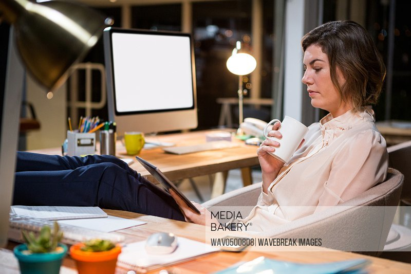 Businesswoman using digital tablet and holding coffee cup at her desk in the office