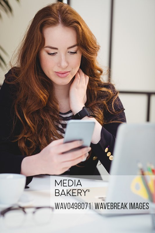 Beautiful young female executive using cellphone at creative office