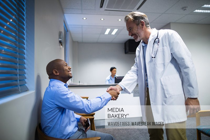 Male doctor shaking hands with patient in hospital