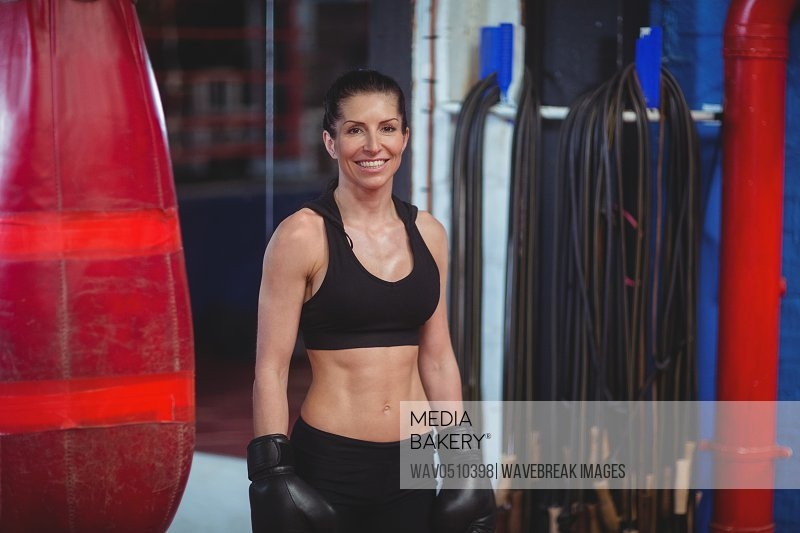 Portrait of smiling female boxer with boxing gloves in fitness studio