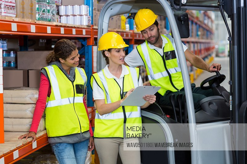 Male and female workers discussing over clipboard in warehouse