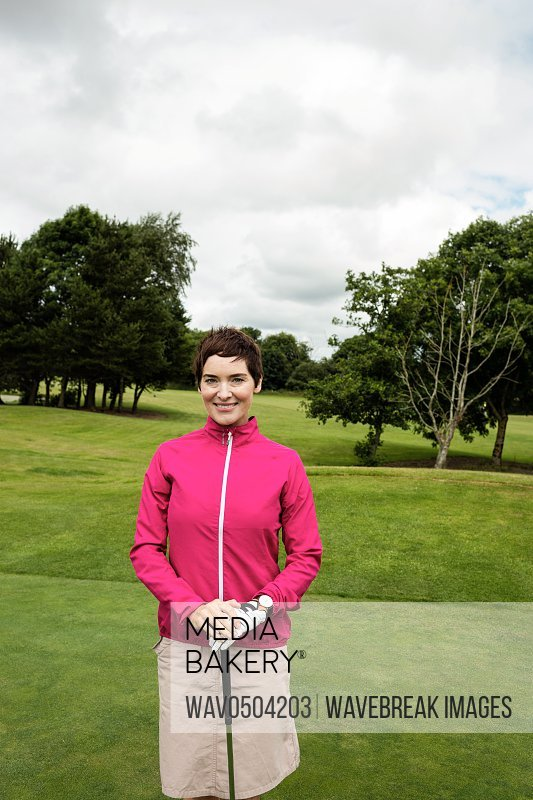 Portrait of smiling woman standing with golf club in golf course