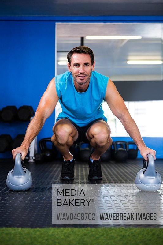 Portrait of smiling athlete with kettlebell while crouching in gym