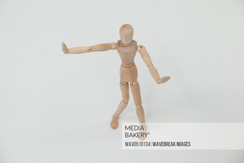 Wooden figurine standing and showing hand stop sign against white background