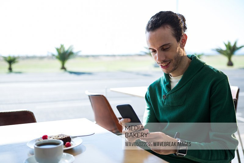 Man using mobile phone with cake and cup of coffee on table in cafeteria