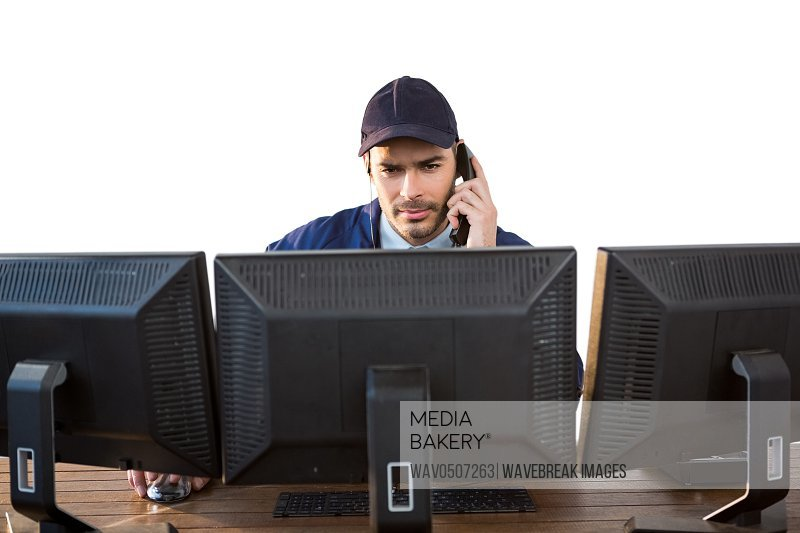 Security officer talking on phone while using computer against white background