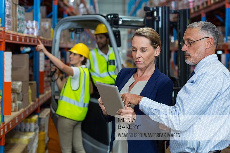 Warehouse manager and client discussing over digital tablet in warehouse