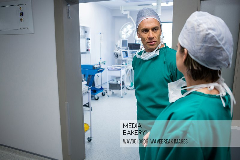 Surgeons interacting with each other in corridor of hospital