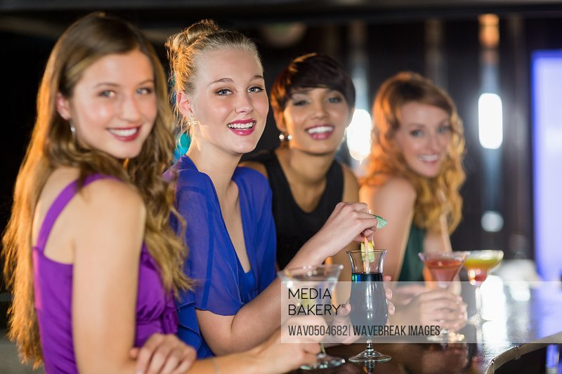 Portrait of smiling friends having glass of cocktail in bar