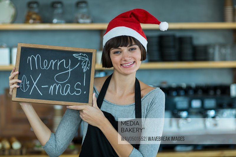 Portrait of waitress showing slate with merry x-mas sign in cafA?