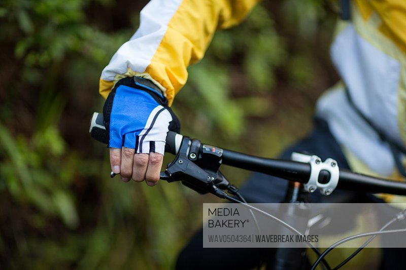 Mid-section of male biker with mountain bike in countryside