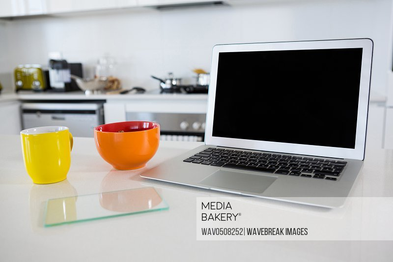 Breakfast bowl with coffee mug and laptop in kitchen at home