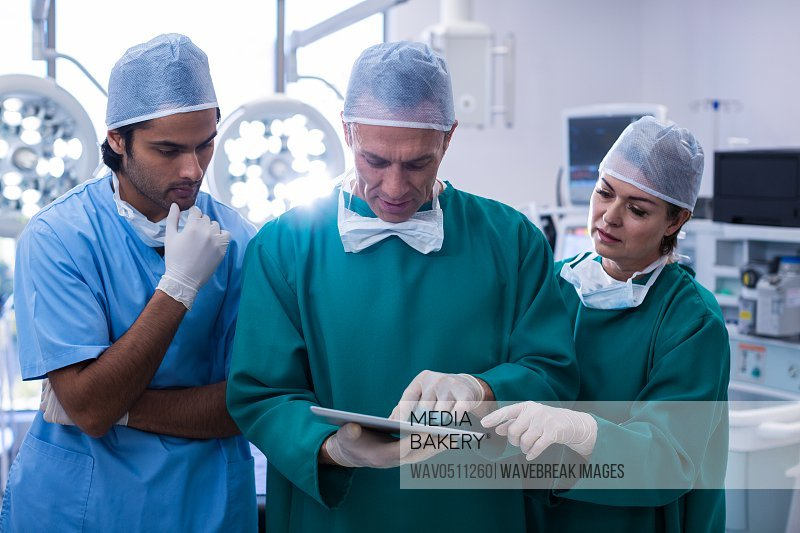 Team of surgeons discussing over digital tablet in operation room at hospital