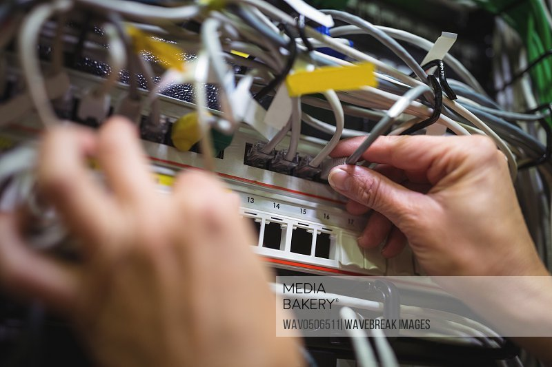 Technician plugging patch cable in a rack mounted server in server room