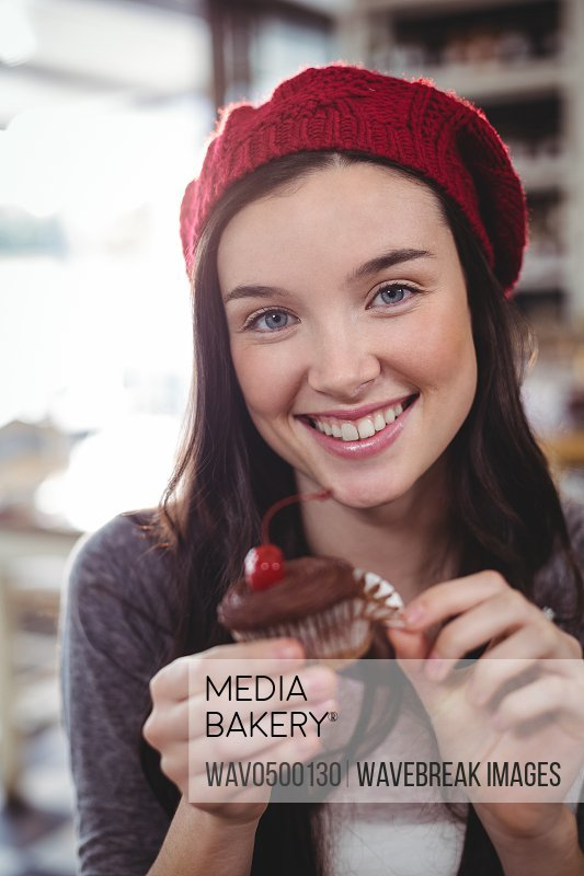 Portrait of smiling woman holding cupcake in cafe