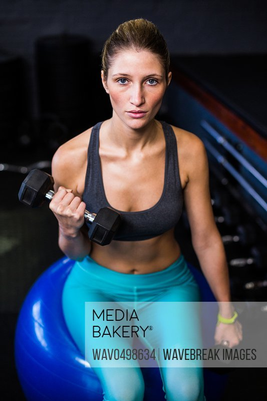 Portrait of woman exercising with dumbbell while sitting on fitness ball