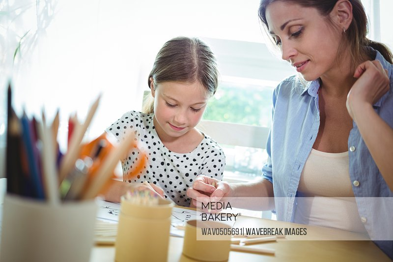 Mother and daughter drawing at table in home