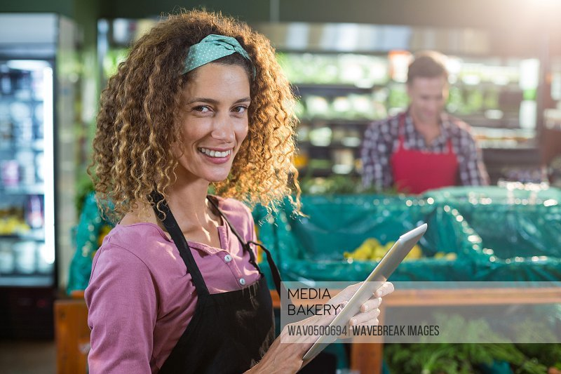 Portrait of smiling female staff using digital tablet in organic section of supermarket
