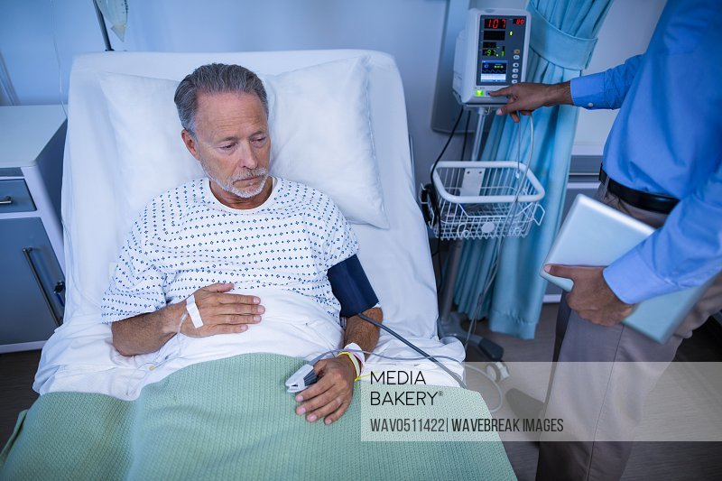 Doctor examining heart rate of patient in hospital