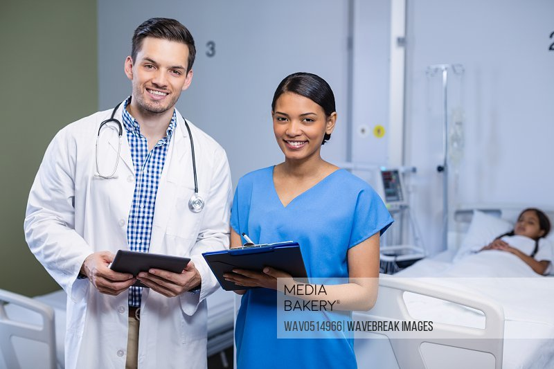 Portrait of doctor and nurse using digital tablet and clipboard